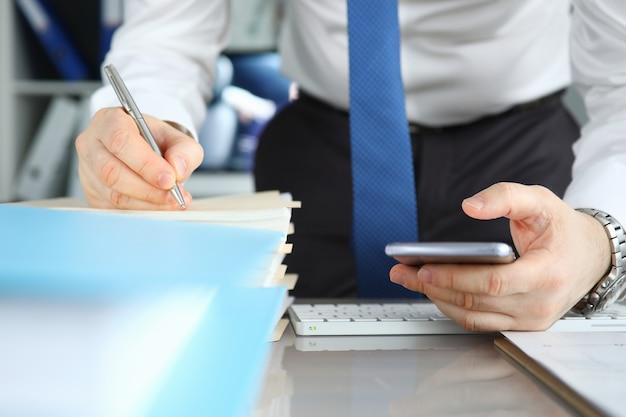 Empresario firma documentos de pila en la oficina de mesa
