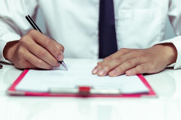 Empresario firmando un documento en la oficina