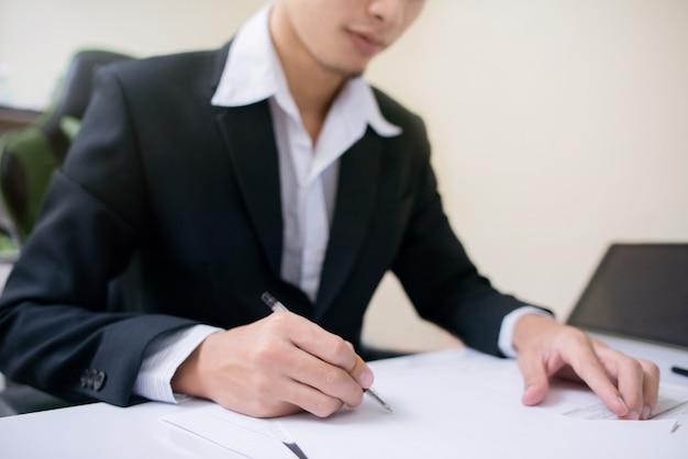 El empresario está firmando a la hoja de papel.