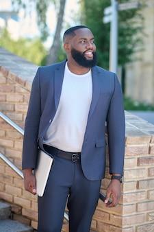 Empresario. una foto de un hombre de piel oscura con un traje y una computadora portátil.