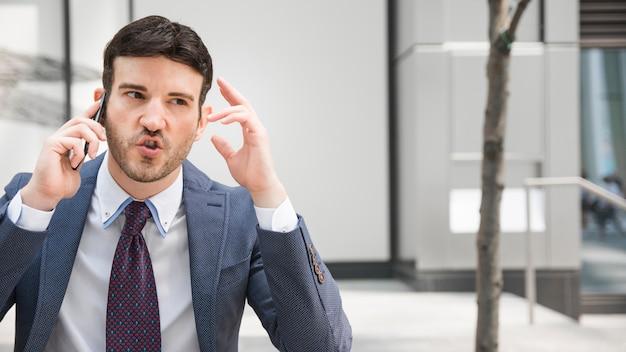 Empresario furioso teniendo conversación telefónica