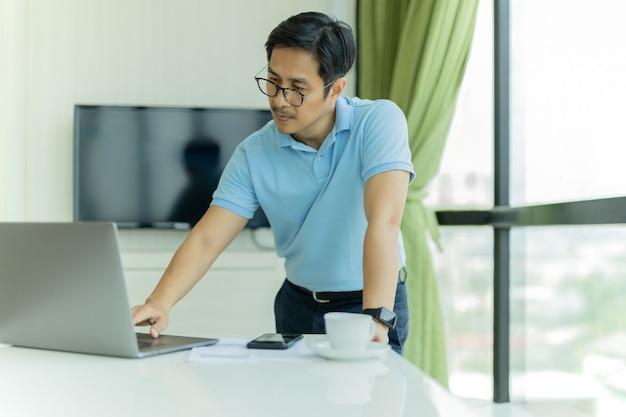 Empresario de gafas inclinado sobre la mesa y trabajar con un portátil en la oficina