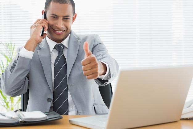 Empresario gesticular pulgares arriba mientras llamada en el escritorio de la oficina