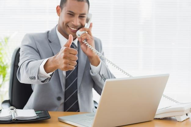 Empresario gesticular pulgares arriba mientras que en la llamada en el escritorio