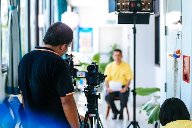 Empresario de grabación de cámara de vídeo dando entrevista al periodista como fondo