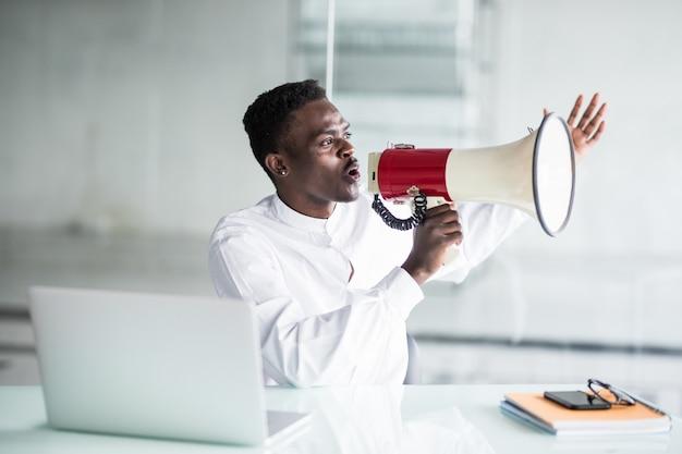 Empresario grita gritando a través de un megáfono en la oficina