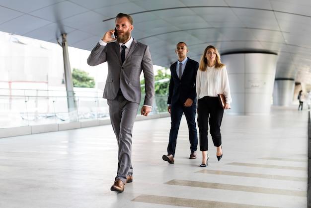 Empresario hablando por teléfono y gente de negocios caminando detrás de él