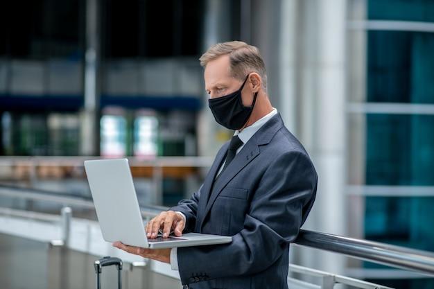 Empresario. hombre adulto serio en traje de negocios y máscara protectora trabajando en la computadora portátil esperando el vuelo en el aeropuerto