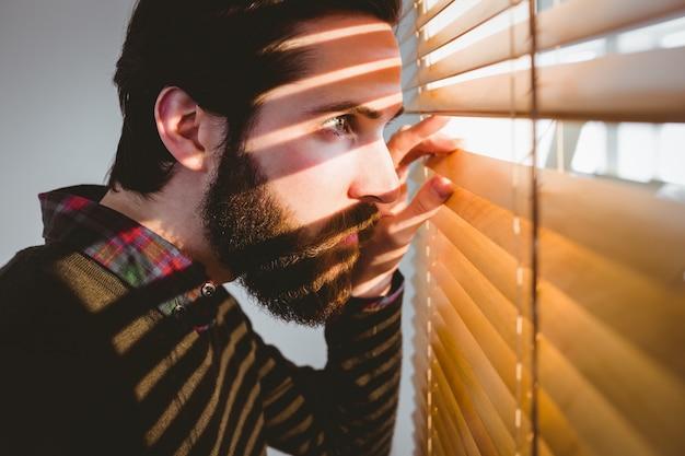 Empresario inconformista mirando a través de persianas