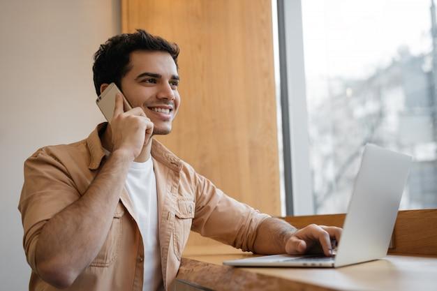 Empresario indio usando laptop, hablando por teléfono celular, trabajando desde casa
