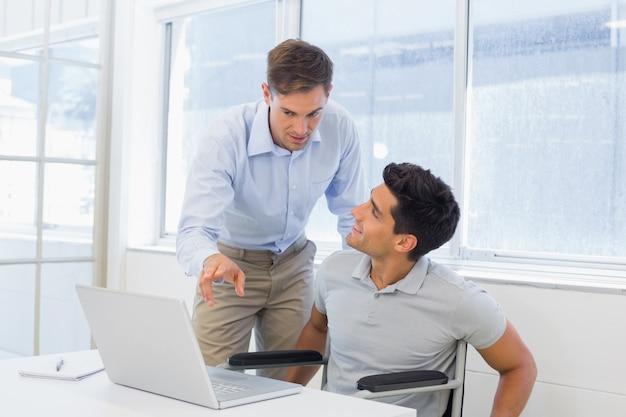 Empresario informal en silla de ruedas hablando con colega usando laptop