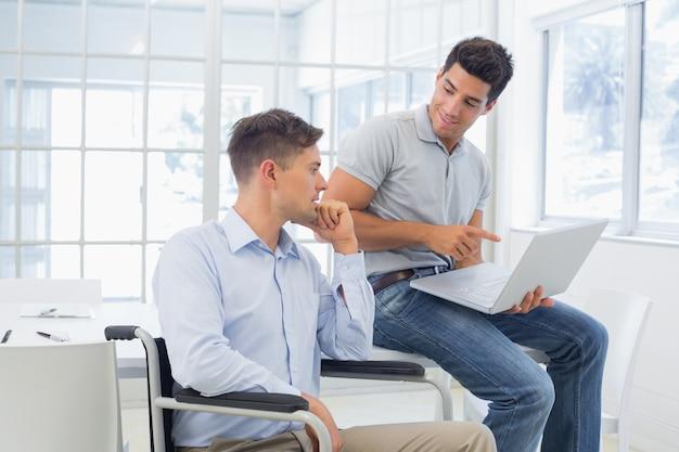 Empresario informal en silla de ruedas hablando con un colega
