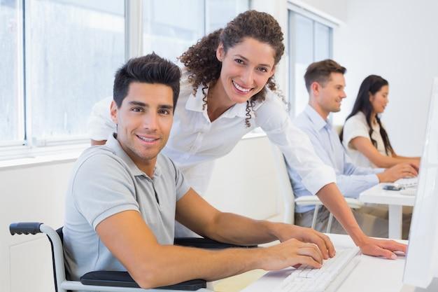 Empresario informal en silla de ruedas trabajando en su escritorio con un colega