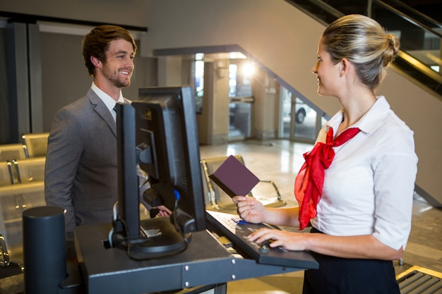 Empresario interactuando con el personal del aeropuerto femenino en el mostrador de facturación