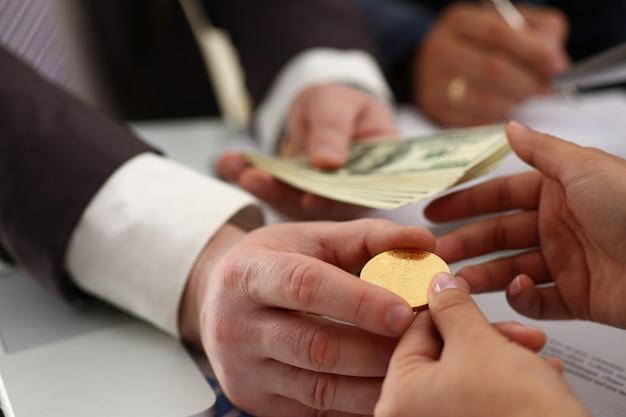 Empresario intercambiando moneda criptográfica por dinero en reunión