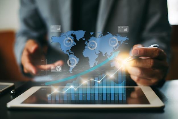 Empresario de inversión analizando el informe financiero de la empresa con gráficos digitales.