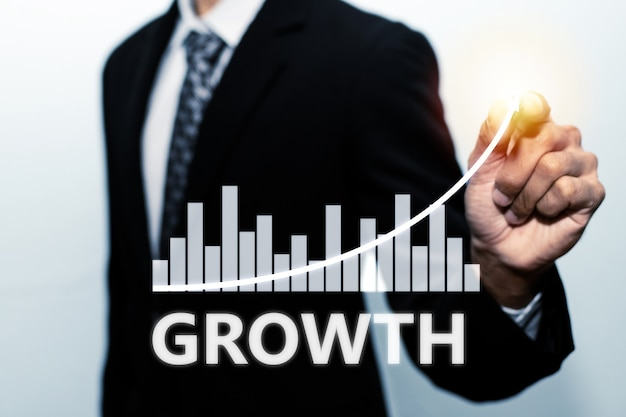 Empresario inversionista mano apuntando con lápiz en la pantalla de gráfico gráfico virtual sobre fondo blanco, mercado de valores, inversión, tecnología digital, estadísticas comerciales y concepto de estrategia empresarial