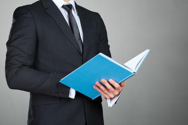 Empresario irreconocible sosteniendo un libro