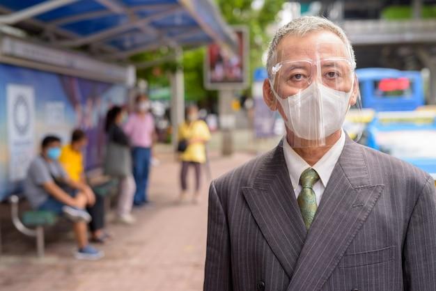 Empresario japonés maduro con máscara y careta en la parada de autobús