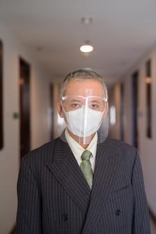 Empresario japonés maduro con máscara y careta en el pasillo