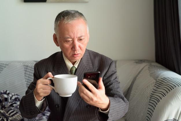 Empresario japonés maduro usando el teléfono y mirando sorprendido en casa
