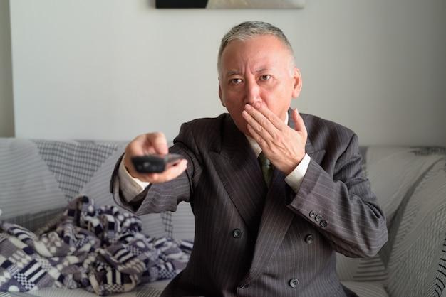 Empresario japonés maduro viendo televisión y mirando sorprendido en la sala de estar en casa