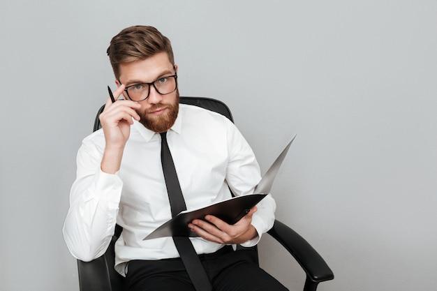 Empresario joven pensativo en anteojos sosteniendo una carpeta