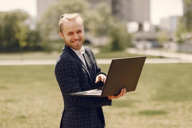 Empresario con laptop en una ciudad de verano