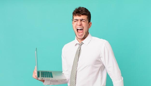 Empresario con laptop gritando agresivamente, luciendo muy enojado, frustrado, indignado o molesto, gritando no