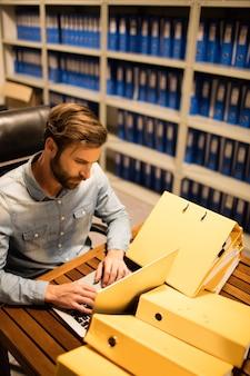 Empresario con laptop en la mesa en la sala de almacenamiento de archivos