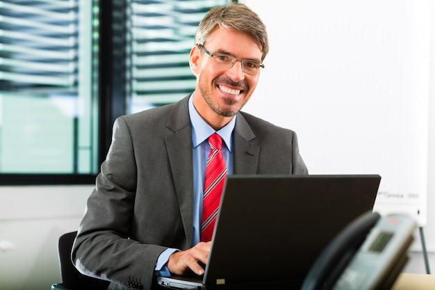 Empresario con laptop en su oficina comercial