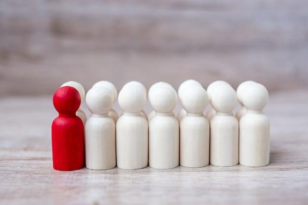 Empresario líder rojo con multitud de hombres de madera. concepto de liderazgo, negocios, equipo, trabajo en equipo y gestión de recursos humanos
