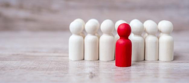 Empresario líder rojo con multitud de hombres de madera. liderazgo, negocios, equipo, trabajo en equipo y gestión de recursos humanos.