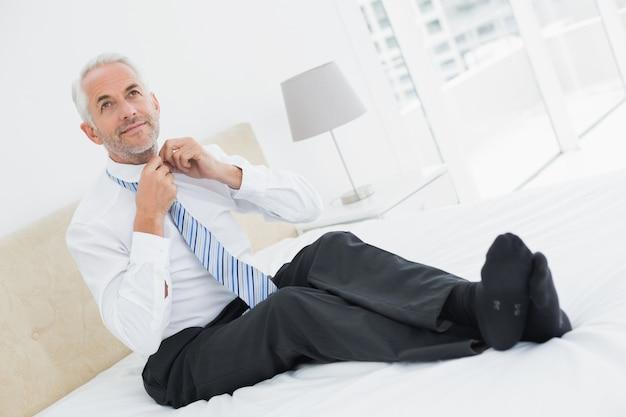 Empresario maduro ajuste corbata en la cama