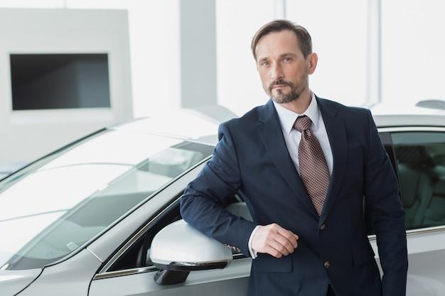 Empresario maduro comprando un automóvil en el salón del concesionario