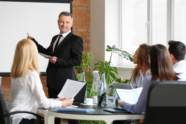 Empresario maduro dando presentación durante la reunión en la oficina