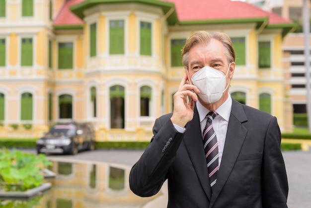 Empresario maduro con máscara hablando por teléfono en la ciudad al aire libre