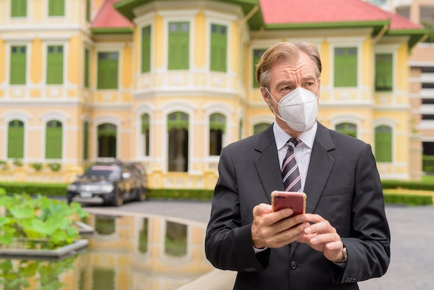 Empresario maduro con máscara pensando mientras usa el teléfono en la ciudad al aire libre