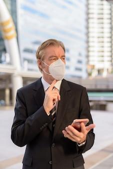 Empresario maduro con máscara pensando mientras usa el teléfono en el puente skywalk