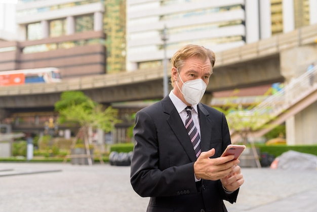 Empresario maduro con máscara pensando y usando el teléfono en la ciudad al aire libre