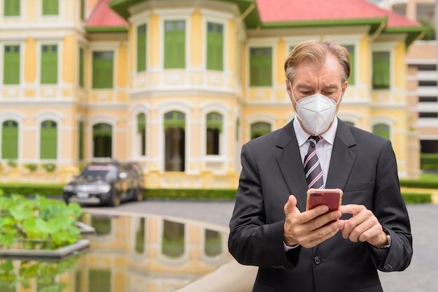Empresario maduro con máscara mediante teléfono en la ciudad al aire libre