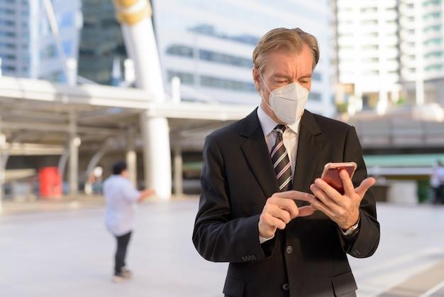 Empresario maduro con máscara mediante teléfono en el puente skywalk