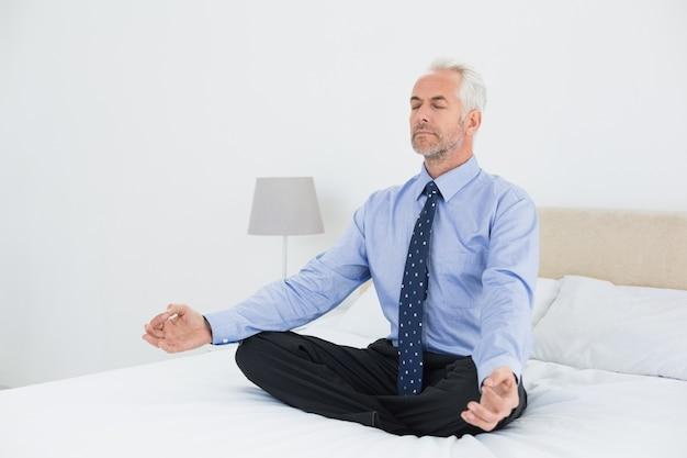 Empresario maduro relajado sentado en postura de loto en la cama