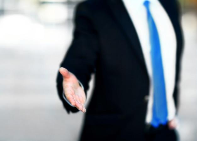 Un empresario con la mano abierta listo para sellar un trato