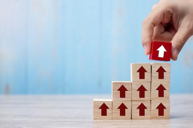 Empresario mano colocando o tirando bloque rojo con flecha y flecha de crecimiento hacia arriba en la mesa