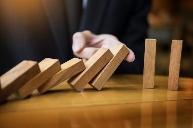 Empresario mano de dominó continuo derribado o riesgo con copyspace.