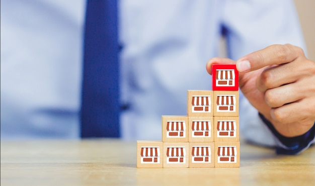 Empresario mano elegir blog de madera con marketing de franquicia