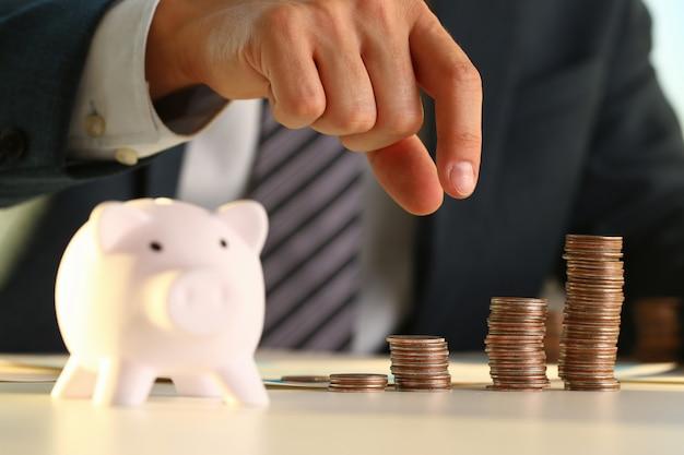 Empresario de mano poniendo dinero pin en cerdo