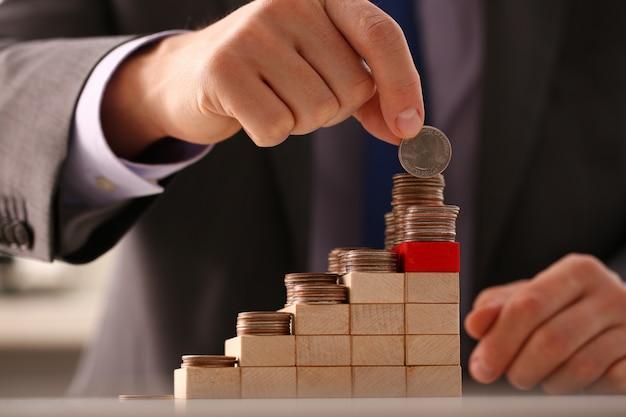 Empresario de mano poniendo dinero pin