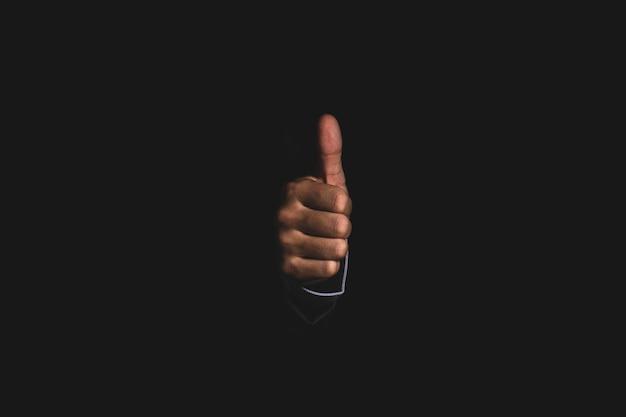 Empresario mano pulgar arriba o como buena señal sobre fondo negro.